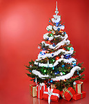 Decorated Christmas tree with gifts under it. Isolated on red background.