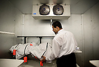 Nathan Vemulapalli (cq) of Adair Funeral Home transports the remains of an unidentified body from the Pima County Medical Examiners Office to a cooler in the funeral home in preparation for cremation and burial in Tucson, Arizona, Thursday, August 6, 2009. The remains are presumed to be from bodies of migrants who died attempting to cross the border into the United States illegally from Mexico...PHOTOS/ MATT NAGER
