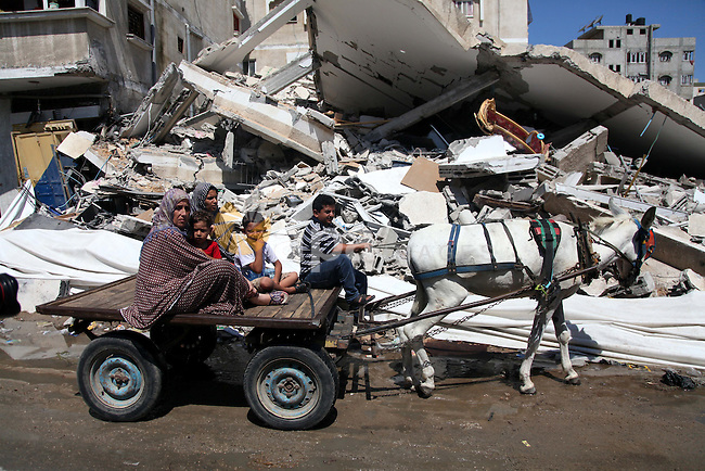 "Palestinians ride a donkey cart past destroyed houses in Gaza city on August 10, 2014. A senior Hamas official said there was a ""weak"" possibility that Gaza truce talks would succeed and that Palestinian negotiators could leave Cairo after a meeting with Egyptian mediators. Photo by Ezz al-Zanoun"