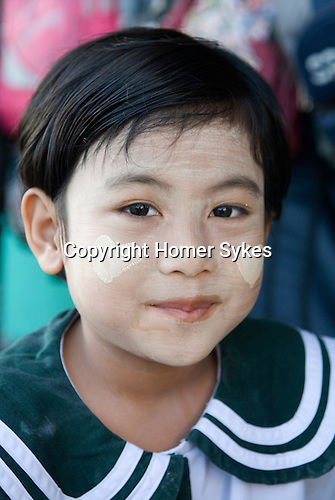 Child in school uniform wearing  makeup Thanakha. A natural product. Two hearts on each cheek. Pathein Burma Myanmar. 2011