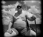 Keith, Glen's counsin drives his boat through the sawgrass of the Everglades. He works for South Florida Water Management.  The Florida Everglades are a disappearing world. Overpopulation, the sugar and cattle industry, mismanagement of the land, droughts and bush fires are just a few of the problems the Florida Everglades are facing. Here Glen Wilsey driving his airboat. According to Glen the best thing about being a tour guide in the everglades is driving the airboats. Riding an airboat is fun but driving an airboat is an awesome feeling.