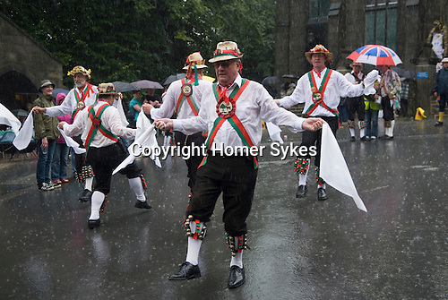 August summer rain. Morris men dance during a rain storm. Uppermill Saddleworth Yorkshire UK 2012