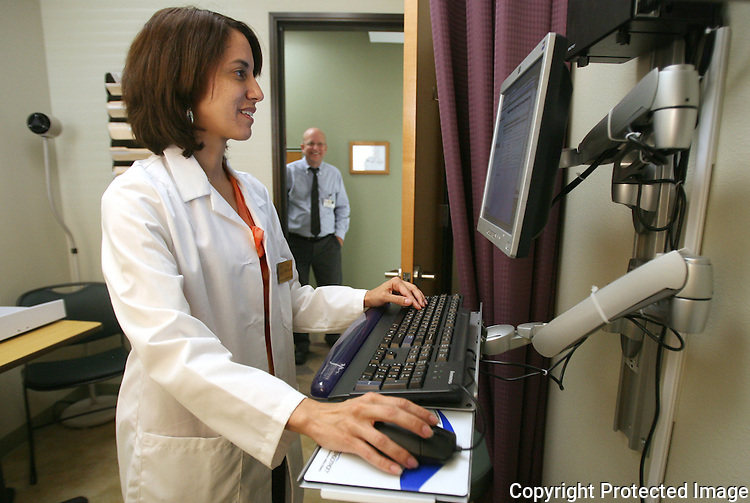 Medical Director of the Vista Community Clinic's newest location, Dr. Kelly Motadel, accesses patients' health records electronically in a pediatric examination room at the new location in 2009.  photo for North County Times
