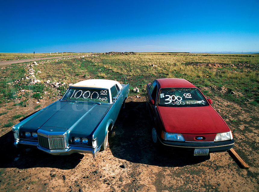 Two old cars out in a desert for sale with their prices written on the windshields.