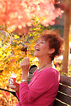Redhead woman blowing bubbles outside, in a park