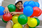 Man sitting with balloons, smiling