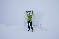 Female hiker celebrates at summit cairn of Matmora in whiteout winter storm, Austvågøy, Lofoten Islands, Norway