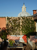 The 1614 Chiesa della Santissima Trinità dei Pellegrini is just behind a jasmine-covered trellis on the terrace; the sofas and cushions are by Manutti.