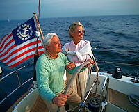 A smiling, relaxed couple on a sailboat.