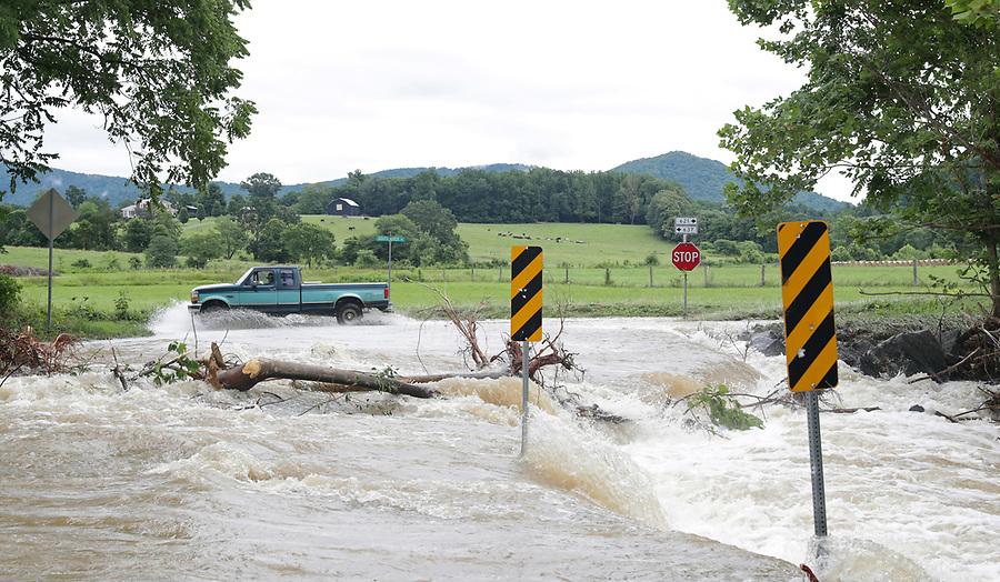 A truck drives past heavy flood waters from the South River at the intersection of Octonia Road and South River Road Friday in Greene County. Photo/Andrew Shurtleff Photography, LLC