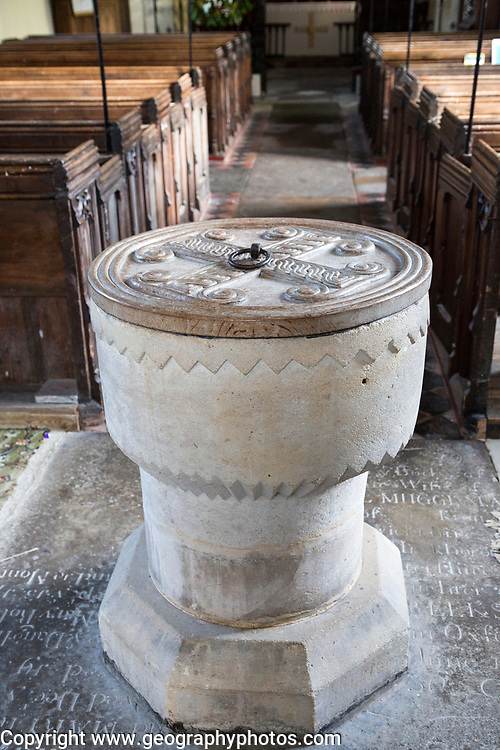 Simply decorated stone 12th century baptismal font inside church at Stanton St Bernard, Wiltshire, England, UK
