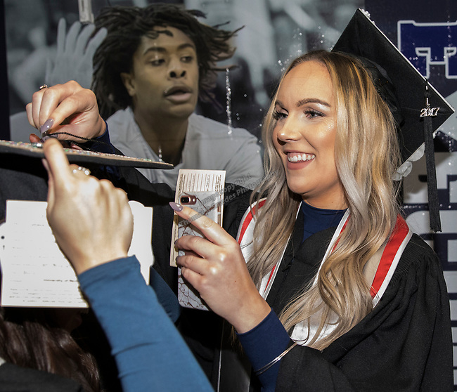 Madison LaRae Petrich (right) helps Connie Voong with her hat during the University of Nevada, Reno afternoon Winter Commencement Ceremony at Lawlor Events Center in Reno, Saturday, Dec. 9, 2017.