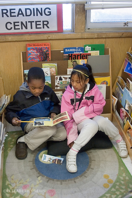 Oakland CA 2nd graders absorbed in books in classroom Reading Center