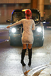 © Joel Goodman - 07973 332324 . No syndication permitted . 01/01/2014 . Manchester , UK . A woman stands in the middle of the road and flags down a taxi . Revellers see in the New Year in Manchester today (January 1st 2014) as police report that officers are at full stretch responding to calls . Photo credit : Joel Goodman