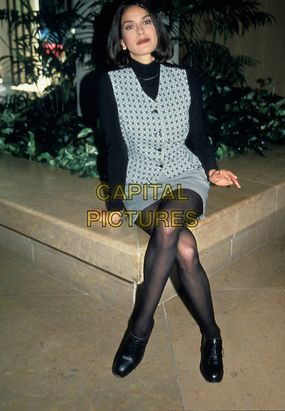 TERI HATCHER.full length seated legs crossed grey gray skirt waistcoat tights black polo neck jumper shoes.www.capitalpictures.com.sales@capitalpictures.com.© Capital Pictures.
