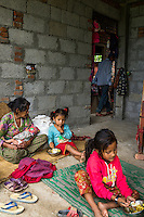 Monika (7, in red) and Aastha Baniya (6, in blue) have lunch while their grandmother Bhagawati Baniya (56) cradles their youngest sister Sapana Baniya (2 months) in their temporary home in Chautara, Sindhupalchowk, Nepal on 29 June 2015. The three girls lost their mother during the April 25th earthquake that completely levelled their house. Aastha was buried under the rubble together with her mother but Aastha survived. As their father Ratna Baniya (28) cannot care for the children on his own, SOS Childrens Villages has since been supporting the grandmother with financial and social support so that she can manage to raise the children comfortably and ensure that they will all be schooled. Photo by Suzanne Lee for SOS Children's Villages