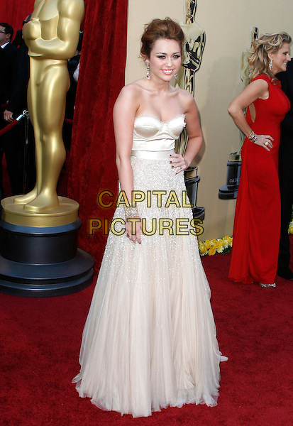 MILEY CYRUS.The 82nd Annual Academy Awards held aat The Kodak Theatre in Hollywood, California, USA..March 7th, 2010.oscars full length strapless white beige dress maxi gown white hand on hip.CAP/EAST.©Eastman/Capital Pictures.