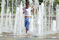 A young girl runs through the Peace Garden Fountains in Sheffield, South Yorkshire