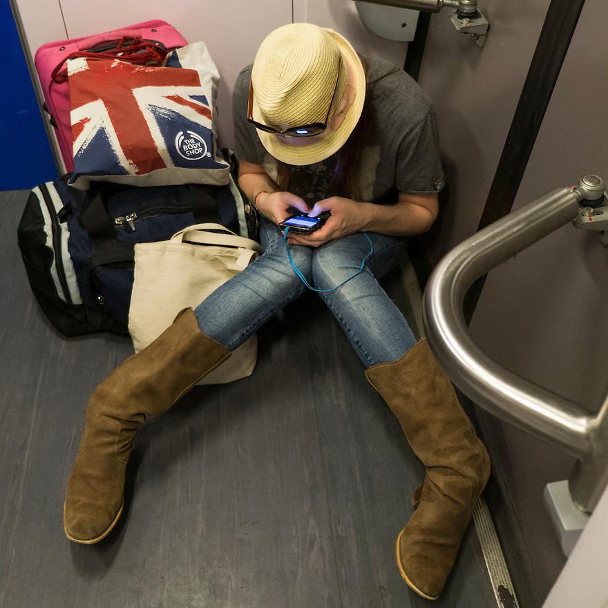 Nederland, Utrecht, 16 aug 2013<br /> Meisje, toerist, in trein zit op de grond bij de deuren te sms'en met haar mobieltje. <br /> Foto(c): Michiel Wijnbergh