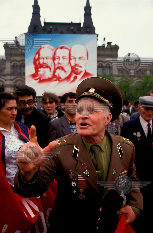 © Paul Lowe / Panos Pictures..Moscow, RUSSIA.  1/5/1990..Retired army colonel, Yerofei Levshov, one of the leaders of the Pamyat party speaking to a crowd at the May day celebrations.  The nationalist and anti zionist Pamyat party believes in the restoration of the Russian monarchy. .For the first time ever and in the spirit of glasnost Moscow City Council allowed protest groups into Red Square after the official ceremonies..Poster of Marx, Engels and Lenin in the background.