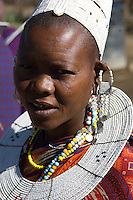 A Masai girl with the traditional shaved head and wearing the traditional hat and ornate beaded earrings, collar and necklaces. A village near the Serengeti National Park, Tanzania.