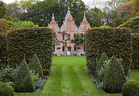 The rear of the house viewed from between meticulously trimmed hedges and elegant, symmetrical flowerbeds