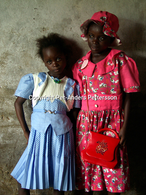 dippchi00012 People Children. Girls. Bebeto Lumueno, age 9, (left) and Chancy Mbungu, age 10 has dressed up and is ready to go to a church service on February 28, 2002 in Ngafani, a village about 20 kilometers outside Kinshasa, Congo. Bebetu is in primary school and wants to be a sewing lady when she grows up. This poor village outside Kinshasa is located close to the Congo River..©Per-Anders Pettersson/iAfrika Photos
