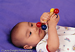 3 month old baby boy closeup, on back, holding toy, looking at hands