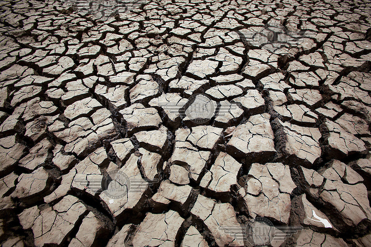 Broken soil on the bed of a dried lake, a result of the dry season.