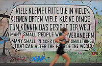 Section of the Berlin Wall depicting a painting by Muriel Raoux and Kani Alavi entitled Afrikanischer Weisheit, with the slogan 'Many small people who in many small places do many small things that can alter the face of the world', damaged by graffiti, part of the East Side Gallery, a 1.3km long section of the Wall on Muhlenstrasse painted in 1990 on its Eastern side by 105 artists from around the world, Berlin, Germany. Picture by Manuel Cohen
