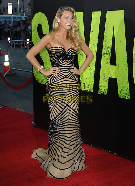 Blake Lively.The World Premiere of 'Savages' held at The Grauman's Chinese Theatre in Hollywood, California, USA..June 25th, 2012.full length black nude beige strapless striped stripes dress train hands on hips.CAP/ADM/KB.©Kevan Brooks/AdMedia/Capital Pictures.