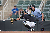 Kannapolis Intimidators catcher Daniel Gonzalez (23) reaches for a pitch as home plate umpire Justin Anderson looks on during the game against the Greenville Drive at Intimidators Stadium on June 7, 2016 in Kannapolis, North Carolina.  The Drive defeated the Intimidators 5-2 in game two of a double header.  (Brian Westerholt/Four Seam Images)