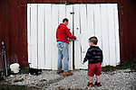 Ford Waterstrat opens the door to his barn with his son Finley, 2, on his organic farm in London, Ky., on Thursday, Oct. 25, 2012.