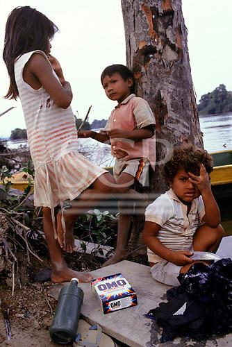 Mato Grosso, Brazil. Rikbaktsa (Canoeiro) children with packet of Omo washing powder and washing by the river.