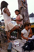 Mato Grosso, Brazil. Rikbaktsa (Canoeiro) children with packet of Omo washing powder and washing by the river.