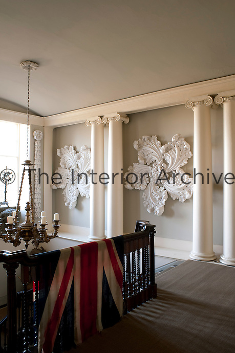 The balustrade on the landing at Aynhoe Park is draped in a Union Jack and the walls of the stairwell are decorated with ornate plaster flowers