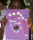 Mabinty Sesay 7 from Virginia, who lost her 5 year old sister Sarah from a sudden unexplained death, shows off her feelings page from her memory book she is making  during art therapy on Saturday July 30, 2005. Mabinty is attending a three day weekend program at the Point of Hope Camp. Point of Hope is a grief camp helping survivors cope with the recent loss of a loved one in Darlington, Md. Mabinty choose the color purple for her page because her sister liked the colors purple and pink. Jane Therese for Newhouse News Service.