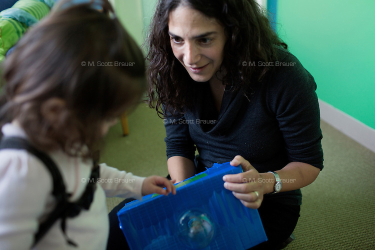 Dr. Laura Schulz, primary investigator in the Early Childhood Cognition Lab in the Department of Brain and Cognitive Sciences, works with Madeline Wilson in the Early Childhood Cognition Lab at MIT in Cambridge, Massachusetts, USA.  The backpack worn by Madeline holds a microphone that records her speech during the experiment.