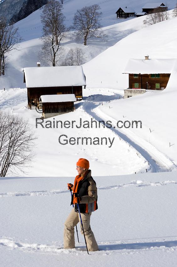 Switzerland, Canton Uri, Urigen: mountain village at Schaechen Valley - woman hiking in deep snow