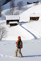Switzerland, Canton Uri, Urigen: mountain village at Schaechen Valley - woman hiking in deep snow