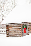 A snow covered log cabin is decorated for christmas in Jackson Hole, Wyoming.