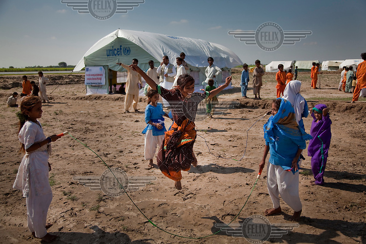Young girls jumping skipping ropes in a child protective space at a UNICEF camp for flood affected people.