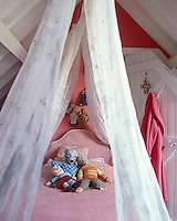 A child's tiny bedroom is situated under the eaves