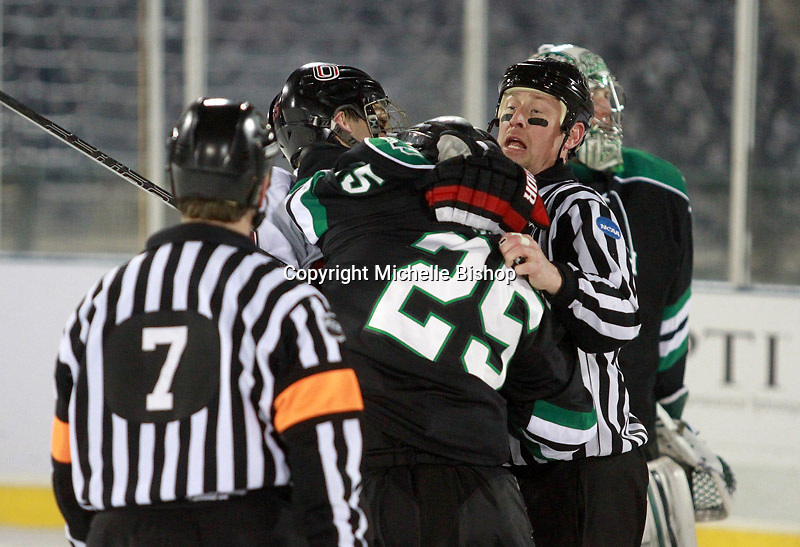 Linesman Chad Evers tries to separate North Dakota's Mitch MacMillan and Nebraska-Omaha's Brent Gwidt. North Dakota beat Nebraska-Omaha 5-2 in the outdoor game at TD Ameritrade Park on Saturday, Feb. 9, 2013. (Photo by Michelle Bishop)