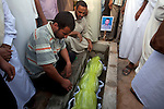 Family members around the body of Khaled Ali Abel Kasm Mussa, 29, placed in a tomb during the burial of eight bodies found last week in a mass grave near the town of Al-Qala in the Nefusa Moutains, Libya, Friday, Sept. 30, 2011. The eight were reburied next to 35 bodies found in a separate mass grave in the area. Members of the Amazigh indigenous tribe, the men were arrested from their homes and at checkpoints by pro-Gaddafi forces, imprisoned, and finally executed sometime in June. The men, many of them related as fathers and sons, or as brothers, were missing until the first, larger mass grave was found in mid-August.