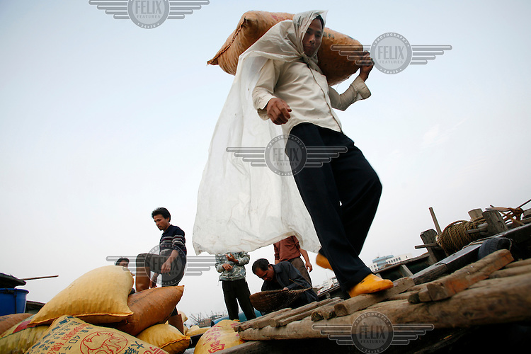 Workers unload sacks of harvested clams from a fishing boat in Beihai.