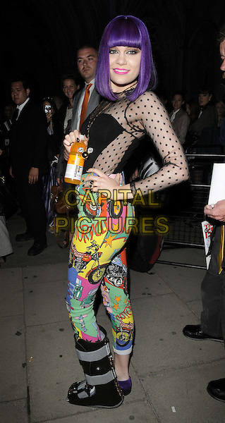 Jessie J (Jessica Ellen Cornish).The Giles catwalk show, London Fashion Week, Royal Courts Of Justice, the Strand, London, England..September 19th, 2011.LFW full length black sheer polka dot top cartoon comic green red yellow print trousers side hand on hip drink beverage cast foot injury wound purple wig hair.CAP/CAN.©Can Nguyen/Capital Pictures.