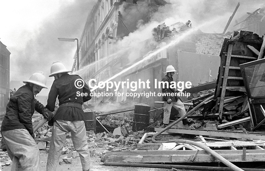 Firemen hose down the smouldering remains of the Chlorane Bar, Gresham Street, Belfast, N Ireland, following an explosion. On 5th June 1976, 10 days earlier, the bar had been the scene of a UVF gun attack in which 5 died, among them the owner, 64 year old James Coyle, from West Belfast. 1976061150315b.<br />