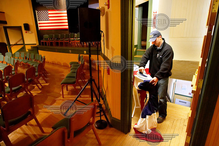 Campaign volunteer Justin Yarborough irons bunting before the start of a town hall meeting with John McCain, Republican candidate for President, during the New Hampshire primary campaign. The Town Hall Meeting form of direct government was pioneered in New England and still governs most towns. Candidates now hold events called Town Hall Meetings hoping to draw on the direct democracy tradition.