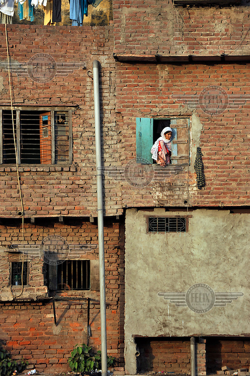 A woman looks out a window in a slum in the area of Nizamuddin East.